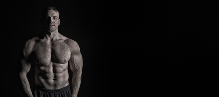 Foto de sexy muscular male torso and body with hairy chest of handsome macho man or athlete guy workout or training on black background - Imagen libre de derechos