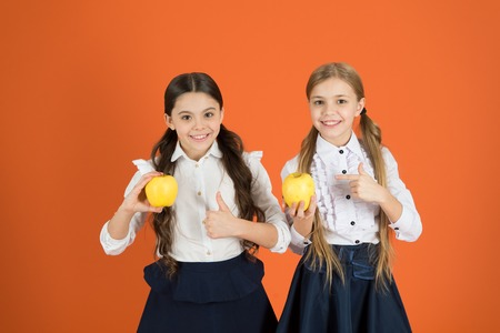 Photo pour School lunch. Vitamin nutrition during school day. Boost student acceptance of fruit. Distributing free fresh fruit at school. Girls kids school uniform orange background. Schoolgirls eat apples. - image libre de droit