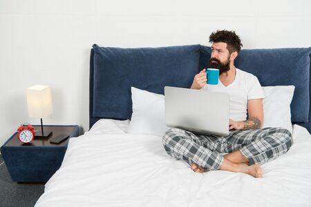 Foto de Hipster bearded guy pajamas freelance worker. Remote work concept. Social networks internet addiction. Online shopping. Man surfing internet or work online. Just woke up and already at work - Imagen libre de derechos