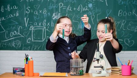 Photo pour Make studying chemistry interesting. Educational experiment concept. Girls classmates study chemistry. Microscope and test tubes on table. Perform chemical reactions. Basic knowledge of chemistry - image libre de droit