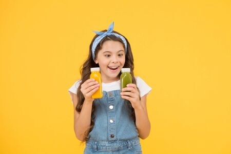 Photo pour Because juice tastes good. Happy small child hold bottles of juice. Little girl enjoy drinking fruit juice. Juice as healthy part of childs diet - image libre de droit