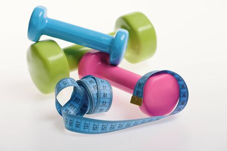 Photo pour Barbells next to cyan measure tape, close up. Dumbbells made of green, blue and pink plastic and rolled ruler on white background. Fit shape and sport concept. Health regime and fitness symbols. - image libre de droit