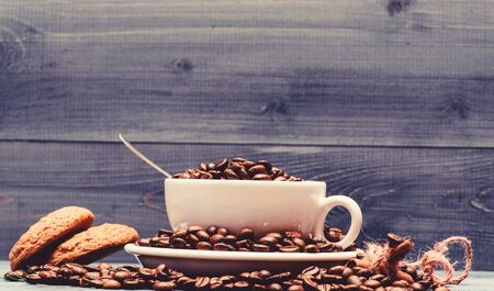 Foto de Coffee break with oat cookie. Beverage for inspiration and energy charge. Cup full coffee brown roasted bean blue wooden background. Fresh roasted coffee beans. Caffeine concept. Cafe drinks menu - Imagen libre de derechos