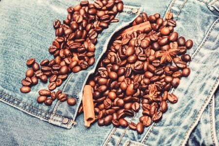 Foto de Coffee shop or store. Fresh roasted coffee close up. Beans and spices in jeans pocket. Degree of roasting coffee beans. Coffee for inspiration and energy charge. Texture and background concept. - Imagen libre de derechos