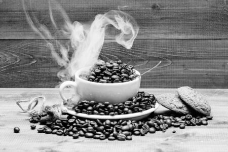 Foto de Degree of roasting grain. Cafe drinks menu. Fresh roasted coffee beans. Coffee for inspiration and energy charge. Cup full coffee brown roasted beans white clouds of smoke blue wooden background. - Imagen libre de derechos