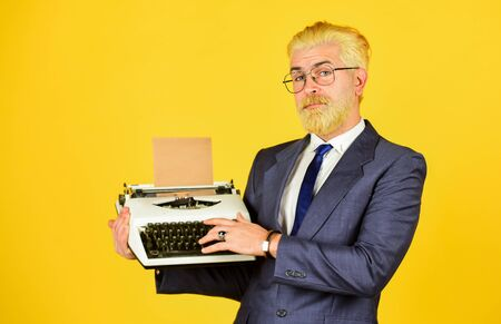 Foto de Salesman vintage objects. Mature man dyed beard hair yellow background. Used goods store. Connoisseur of vintage values. Vintage typewriter. Writer stick old habits. Businessman use retro technology - Imagen libre de derechos