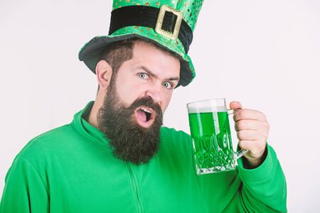 Photo pour Take it easy this paddys day. Irish man with beard drinking green beer. Celebrating saint patricks day in bar. Hipster in leprechaun hat holding beer mug. Bearded man toasting to saint patricks day - image libre de droit