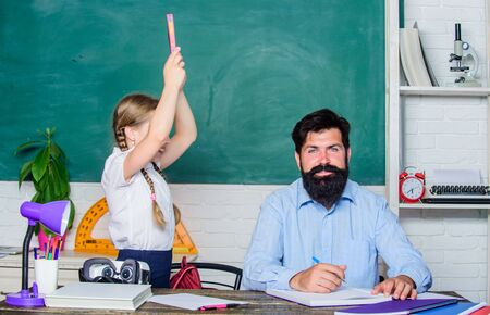 Foto de Help study. Discipline and upbringing. Man bearded pedagogue study together with kid. Study is fun. School teacher and schoolgirl. Homeschooling with father. Reward and punishment principle - Imagen libre de derechos