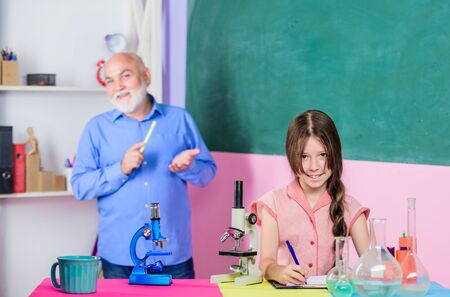 Foto de Teacher help schoolgirl. School lesson. Good pedagogue friendly kind. Little girl with man tutor study science. Pedagogue career. Experienced pedagogue. Expand your mind. Chemistry and biology - Imagen libre de derechos