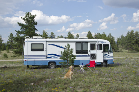 Photo pour A Golden Retriever dog sits in front of his camper - a Class A motorhome. - image libre de droit