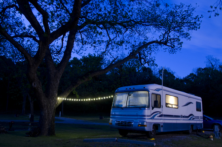 Photo pour A large motorhome sits under a huge pecan tree, lit up as night falls on the campsite. - image libre de droit