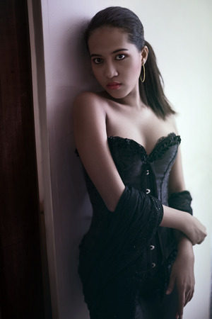 Photo pour Model in corset lingerie looking at camera with sexy cleavage and golden earring - image libre de droit