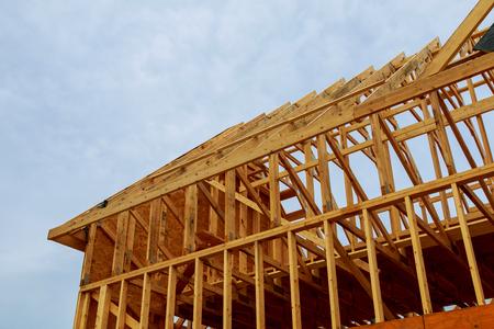 Photo pour A new wooden frame on a house under construction in a blue sky - image libre de droit