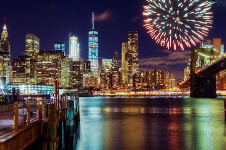 Foto de Firework over city at night with reflection in water Fireworks on the background of New York - Imagen libre de derechos