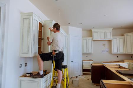 Photo pour Installation of kitchen. Worker installs doors to kitchen cabinet. Installation of doors on kitchen cabinets - image libre de droit