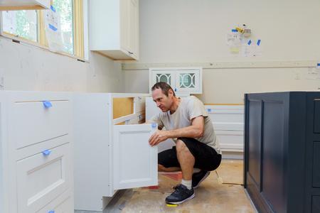 Foto de worker installing kitchen cupboard Installation of kitchen. Worker installs kitchen cabinet. - Imagen libre de derechos