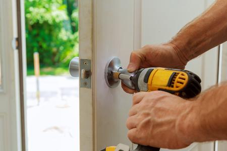 Foto de Installation of a lock on the entrance door Hand 's man with screwdriver Installs door knob. - Imagen libre de derechos