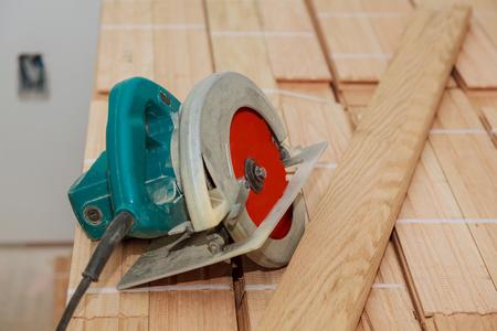 Photo pour Electric saw on wood floor in progress cut old parquet floor with electric saw - image libre de droit