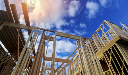 Photo pour Framed beam construction home framing over blue sky - image libre de droit