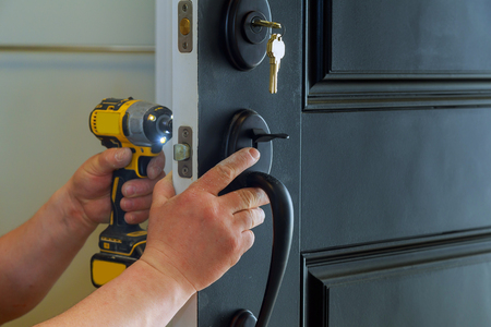 Foto de Closeup of a professional locksmith installing a new lock on a house exterior door with the inside internal parts of the lock - Imagen libre de derechos