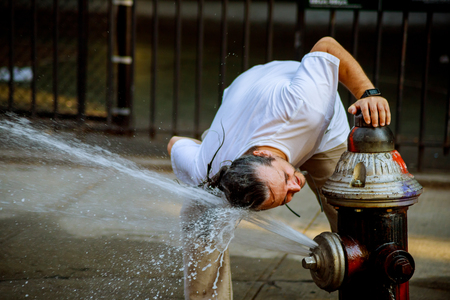 Foto de A strong heat temperature and the man is refreshed with water from a fire hydrant - Imagen libre de derechos