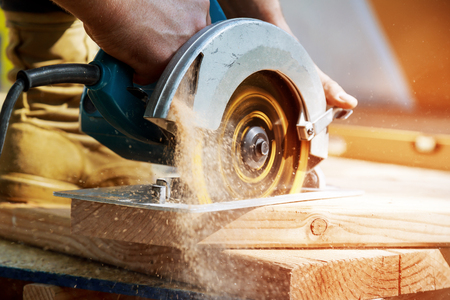 Photo for New home constructiion project building contractor worker using hand held worm drive circular saw to cut boards - Royalty Free Image