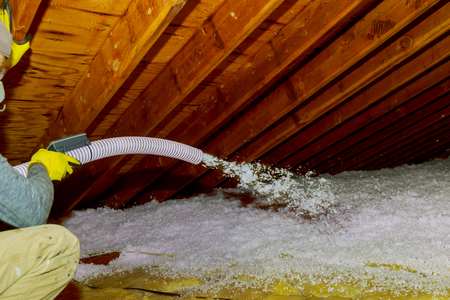 Photo pour Technician spraying blown Fiberglass Insulation between Attic Trusses foam insulation repair tool in the white protect suit applies a construction foam from the gun to the roof. - image libre de droit