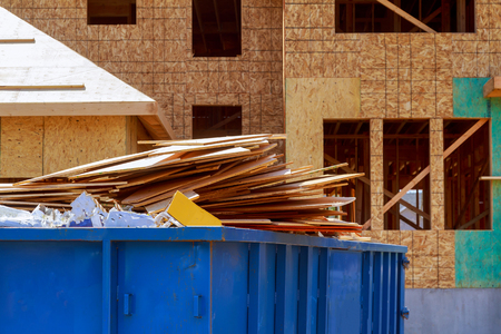 Photo for Residential view of new houses being built and construction garbage large container - Royalty Free Image