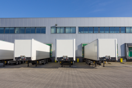 Photo pour Trailers at docking stations of a distribution center waiting to be loaded - image libre de droit