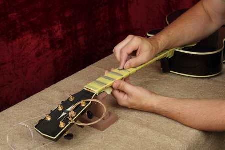 Photo for Musical instrument guitar repair and service - Worker polishing guitar neck frets Sandpaper - Royalty Free Image