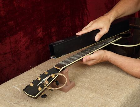 Photo for Musical instrument guitar repair and service - Worker grinds black guitar neck frets. - Royalty Free Image