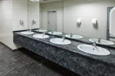 Row of wash basins with mirrors in public toilet