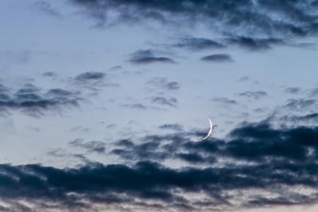 Foto de Young moon in the evening sky with dark clouds - Imagen libre de derechos