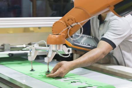 Foto de The technician operator adjust the automatic robot arm. Industrial 4.0 concept.Modern technology for manufacturing - Imagen libre de derechos