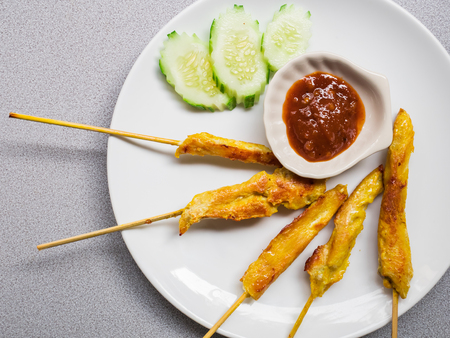 Photo for Thai traditonal food- Chicken satay  with peanut sauce on white plate - Royalty Free Image