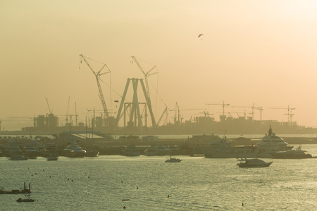 Tourism yachts docked near Jumeirah Beach with massive construction of buildings in the background and a parachutist in the sky, Dubai, United Arab Emirates