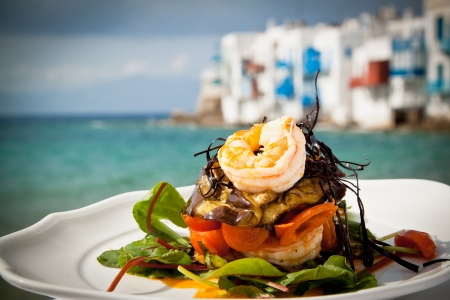 Prawn starter with aubergine, tomato and salad by the sea in Mykonos, Greece