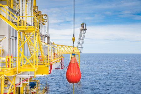 Foto de Pedestal crane annual inspection, crane pull load test activity at offshore oil and gas platform by used orange water bag simulate load. - Imagen libre de derechos