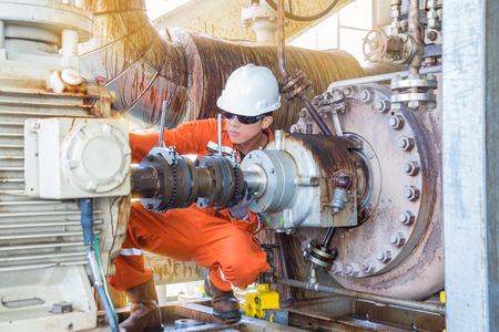 Photo for Offshore Oil Rig worker, Mechanical technician inspecting oil centrifugal pump alignment to prevent vibration which damage bearing and mechanical seal systems. - Royalty Free Image