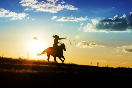 Photo for Girl loses hat while riding horse at sunset - Royalty Free Image