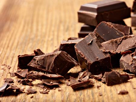 Photo pour close up of chocolate pieces on  wooden background - image libre de droit