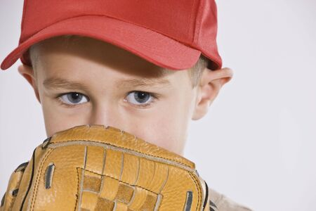 A young boy is wearing a baseball cap and holding a baseball mitt up to his face. Horizontally framed shot.