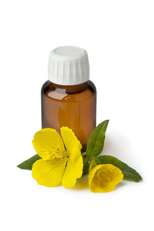 Foto de Bottle with  Evening Primrose oil and fresh flower on white background - Imagen libre de derechos