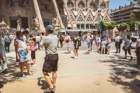 Foto de BARCELONA, SPAIN - June 21, 2017 : tourists making pictures in front of the Sagrada Familia, a wide Roman Catholic church designed by Catalan architect Antoni Gaudi - Imagen libre de derechos