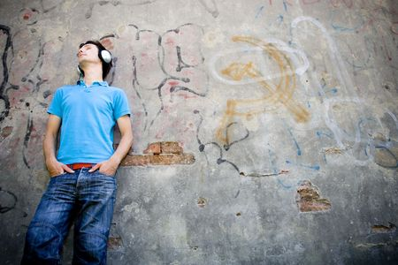 Man leaning against wall with graffiti