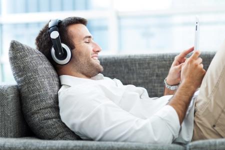 Foto de Man on sofa with headphones and digital tablet - Imagen libre de derechos