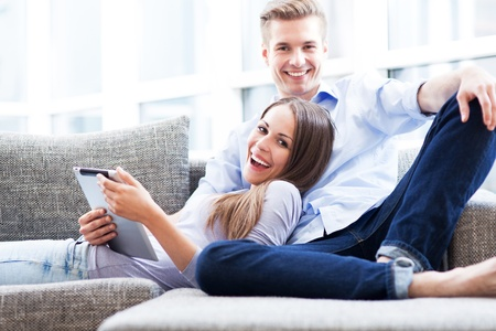 Photo for Couple on sofa with digital tablet - Royalty Free Image