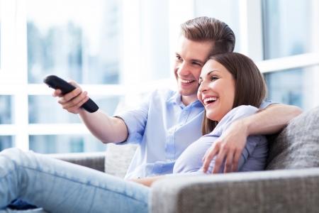 Foto de Couple on sofa with TV remote - Imagen libre de derechos
