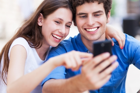 Photo pour Young couple looking at mobile phone - image libre de droit