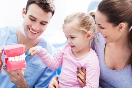Dentist teaching girl how to brush teeth
